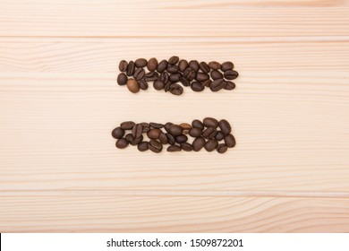 Equal sign. A mathematical equal sign that is collected from roasted coffee beans. Grains lie on a wooden textured countertop in light colors.