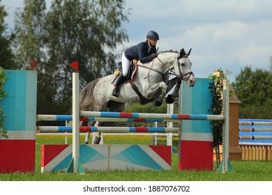 Equestrian girl jumping sportive horse