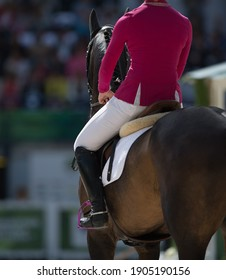equestrian horse rider in saddle from behind wearing red horse show jacket white jodhpurs and tall black boots