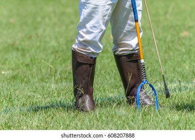 Equestrian Polocrosse Player Boots Racket Polocrosse player closeup unidentified walking boots rackets  equestrian sport equipment.
