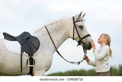 Equestrian rider girl with a white arabian horse.