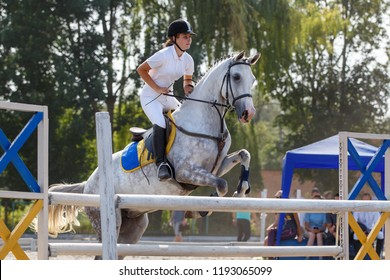 Equestrian sport. Young girl jumping over obstacle on show jumping competition