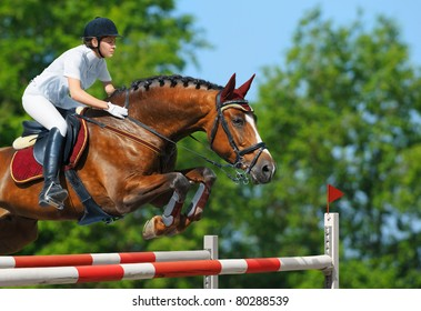 Equestrian sport - young woman jumping with bay horse