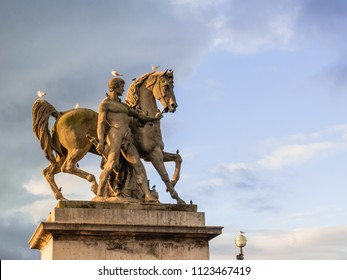 Equestrian statue of roman knight stands, full of birds, by the Seine river, in Paris, France.