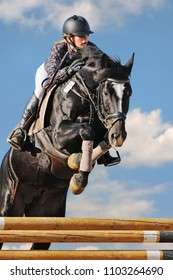 Equestrianism: Young girl in jumping show against blue sky