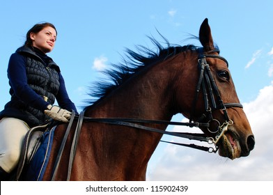 Equestrienne rides front of blue sky
