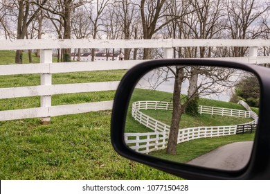 Equine fences along hillside in side-view mirror of car on rural road near equine fence in Kentucky bluegrass country