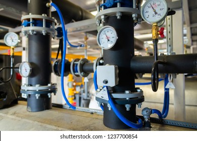 The equipment of the boiler-house, valves, tubes, pressure gauges, thermometer. Close up of manometer, pipe, flow meter, water pumps and valves of heating system in a boiler room