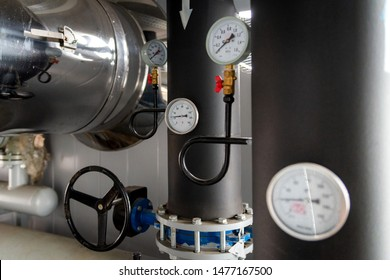 The equipment of the boiler-house, - valves, tubes, pressure gauges, thermometer. Close up of manometer, pipe, flow meter, water pumps and valves of heating system in a boiler room