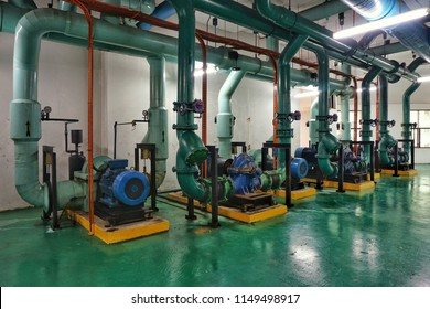 Equipment, cables, motor pump and piping as found inside of industrial chiller plant room.
