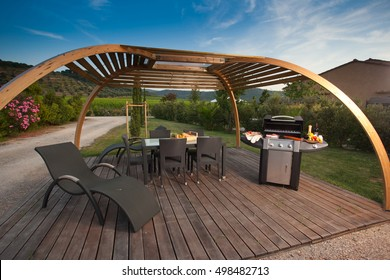 Equipment to do the barbecue with grill and portable fire under a pergola in the shade, cooking the steak Florentine beef and vegetables