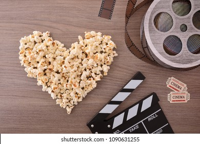 Equipment and elements of cinema on wooden table with popcorn heart. Concept of watching movies. Vertical composition. Top view.