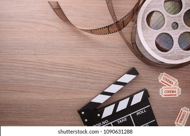 Equipment and elements of cinema on wooden table. Concept of watching movies. Horizontal composition. Top view.