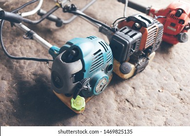 Equipment for gardening. Colorful brush cutters engines lying on the concrete floor.