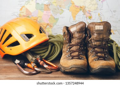 Equipment for high-altitude climbing: boots, sports rope, carbines on the background of the geographical map.
