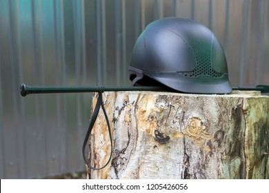 Equipment for horse riding: helmet and whip on the wood
