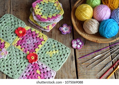 Equipment for knitting and crochet (hook, colorful rainbow cotton yarn, ball of threads, wool, knitted elements, napkin). Granny square. Handmade crocheting crafts. DIY concept. Copy space
