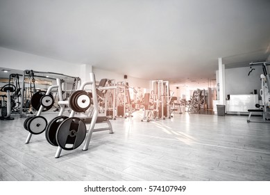 Equipment And Machines At The Empty Modern Gym Room. Fitness Center. Toned image.