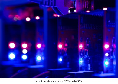 Equipment For Mining Crypto Bitcoin Token, Etherium Cash Close-up. Electronic Boards And Chips, Blue And Red Lights. Blurred Server Lights