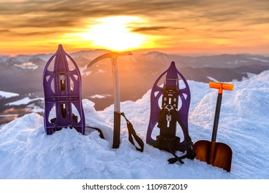 Equipment for mountaineering on the top of a snow-capped mountain on the background of the sun. snowshoeings, ice axis, avalanche shovel, on the glacier