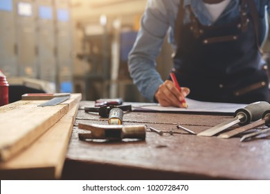 equipment on wooden desk with man working in workshop background.
