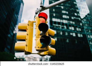 Equipment for regulating transport with lambs hanging in downtown in usa,yellow traffic lights controlling cars and supporting safety on crossways in megalopolis with high buildings and construction