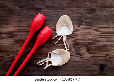 Equipment for rhythmic gymnastics. Clubs and gymnastics shoes on dark wooden background top view copy space