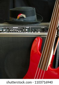 Musician's equipment rig ready for stage performance includes red electric bass guitar, black pork pie hat and amplifier.