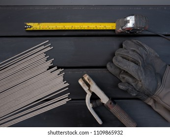 equipment for smith Measuring Tape welding electrodes, electrodes holder and Leather gloves on Steel background