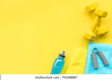Equipment for sport exercise. Fitness background. Dumbbells, expander on pastel yellow background top view copy space