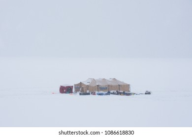 Equipment tent used for scuba diving on a frozen mountain lake in a blizzard