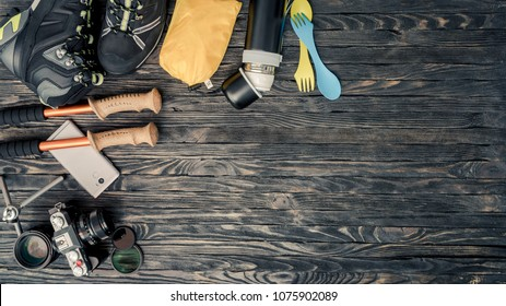 Equipment for trekking and travel on wooden background with copy space. Top view of trekking shoes, trekking pole, digital camera, lenses and thermos