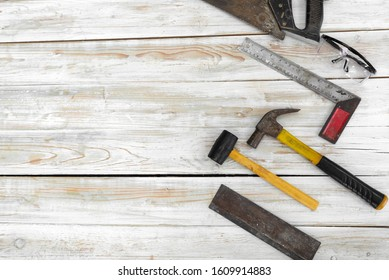 The equipment for woodworking is organized neatly on the wood floor.  Ordered as follows, Hand Saw,  Dustproof glasses, Machinist square, hammer, mallet, Dovetail Saw.