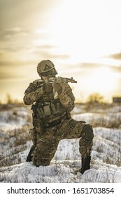 equipped army soldier Man in the winter multicam camouflage is patrolling or patrol field territory. commandos with full equipment helmet and gun watchs winter desert. Modern army soldier. warm photo