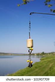 Equipped with a bait for carp, tehnoplankton attached to a fishing rod against the blue sky and the lake