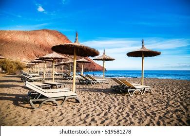 the equipped with chaise-longues and sun umbrellas beach Playa de la Tejita, Tenerife, Canary Islands