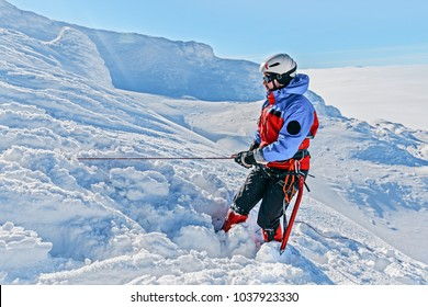 Equipped climber ascent by snowy slope with climbing rope on the top of peak in snowy alpine mountains. Life guard professional man on the work in high mountains. Action in hard conditions scene.