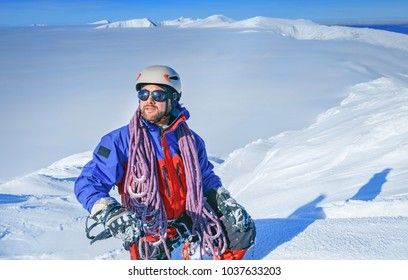 Equipped climber ascent on the top of peak in snowy alpine mountains. Life guard professional man on the work in high mountains.