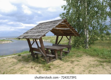 Equipped picnic place (wooden benches and canopy) on the lake shore.
