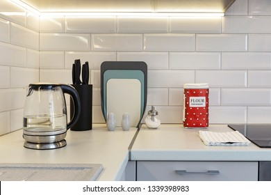 Equipped white kitchen counter: glass kettle, cutting desk. set of knives, spicy accessories, bakery flour in a bright red package and a table cloth
