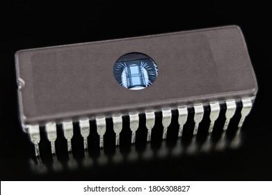 Programmbarer lesbarer Speicher. EPROM-Chip auf schwarzem Hintergrund. Digitale integrierte Schaltungen mit dünnen Silber-Drähten in DIP-Paket mit transparentem Fenster, um Daten durch ultraviolettes Licht zu löschen.
