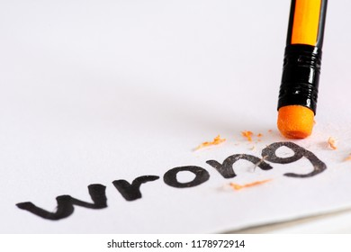 """Erase the word Wrong with a rubber concept of eliminating the error, mistake. closeup of a pencil erasing an """"Wrong""""."""