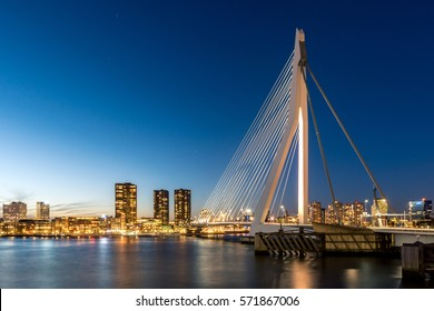 The Erasmus bridge of Rotterdam during the blue hour, the last light of the day. The first stars are showing in the blue sky. On the other site of the river the lights of the city are turned on.