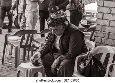 Erbil, Iraq - March 7, 2016: Old Kurdish man drinking hot tea in coffee  shop in Iraq