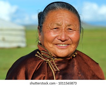 ERDENESANT, MONGOLIA - AUG 13, 2012: Old Mongolian woman wears a silken, brown deel (traditional Mongolian overcoat), stands in front of her yurt and poses for the camera, on Aug 13, 2012.
