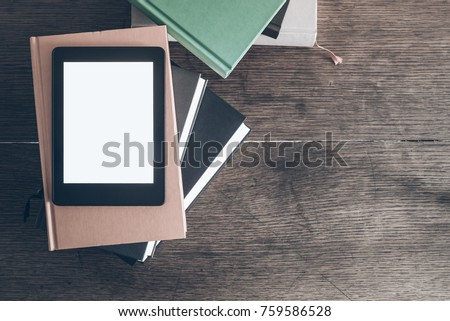 e-reader on stack of books on rustic wooden desk