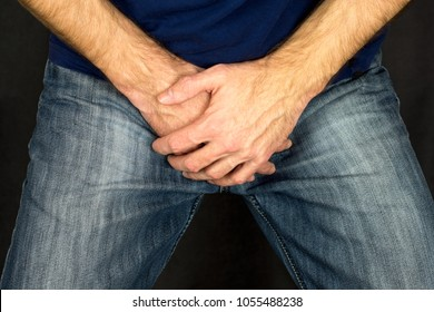 Erectile dysfunction concept. Close up of a man with hands holding his crotch dark background. Men's health. The pain from the blow in groin