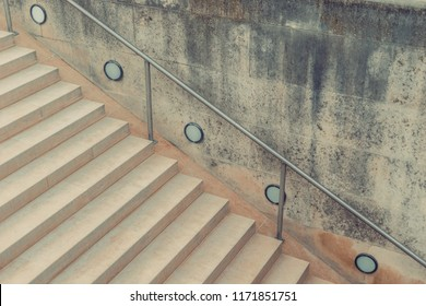 ered vintage marble sandstone travertine stairs with metal handrails and floor lights. Vintage classic geometric concept.