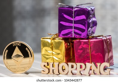 Eretheum coin crypto currency with golden colored gift box and 'SHOPPING' text on wooden table top