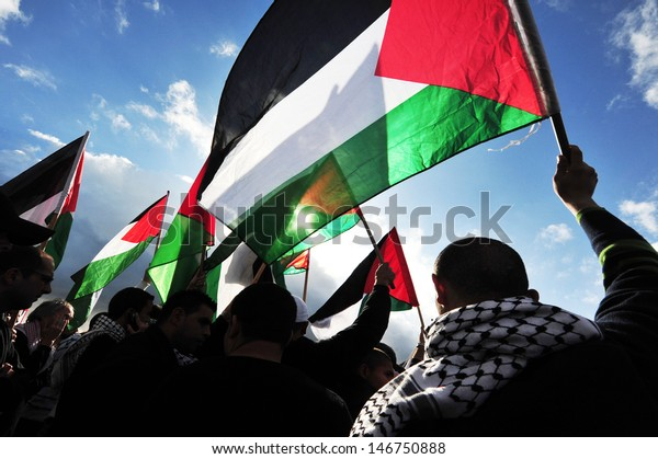 EREZ CROSSING, ISR-DEC 31 2009:Rear view of Palestinians mob carry flag sof Palestine.On April 2013, 132 (68.4%) of the 193 member states of the United Nations have recognized the State of Palestine.